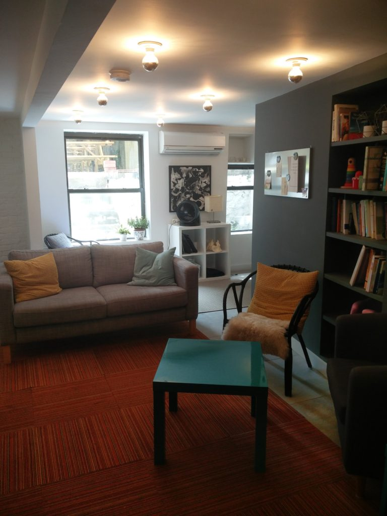 The downstairs area features a sofa and a corner table (at right) for children who need extra quiet to focus.